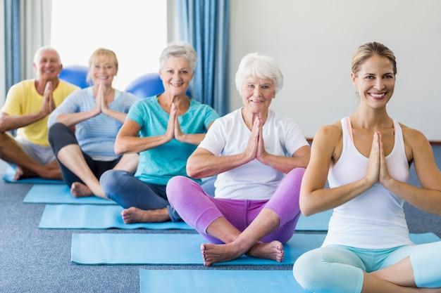 Ausbilder, der yoga mit senioren durchführt