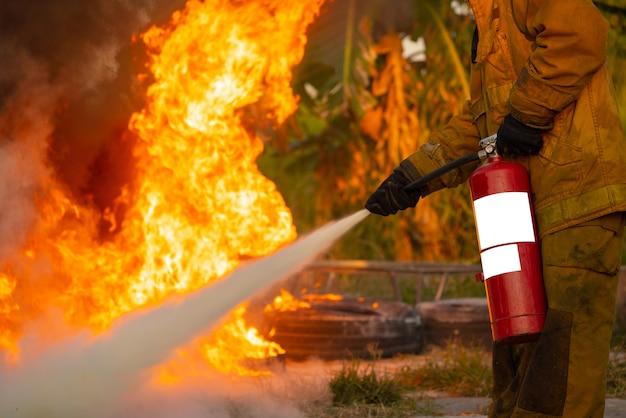 Ausbilder, der zeigt, wie man einen feuerlöscher bei einem trainingsfeuer benutzt