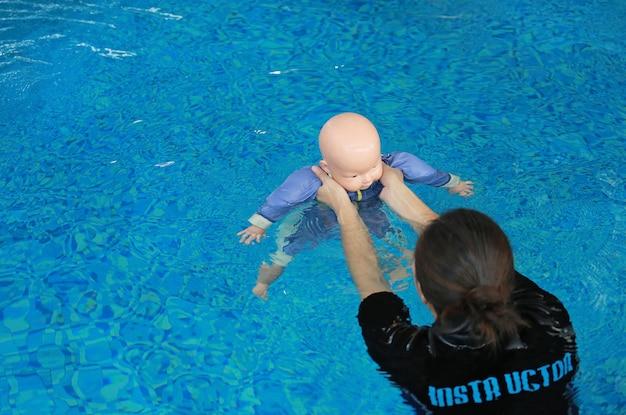 Ausbilder-trainingsattrappe, die baby - puppe im pool ertrinkt.