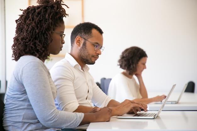 Ausbilder und auszubildender, die zusammen computer verwenden