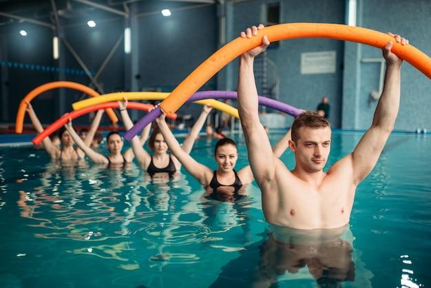 Ausbilder und frauenklasse über fitness-training im schwimmbad. aqua aerobic training, wassersport