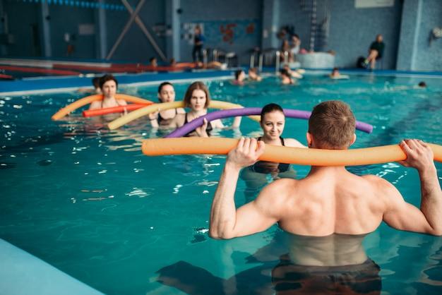 Ausbilder und weibliche gruppe beim training im schwimmbad. aqua aerobic training, wassersport