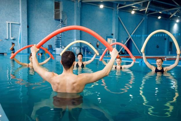 Ausbilder und weibliche gruppe, training im pool