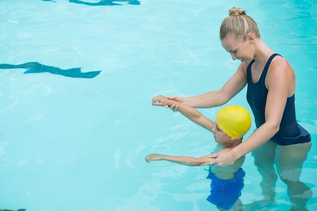 Ausbilderin, die jungen im pool ausbildet