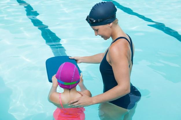 Ausbilderin, die junges mädchen im pool ausbildet