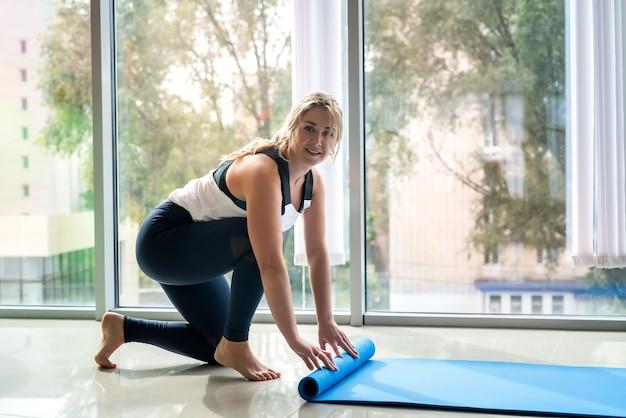 Ausbilderin für pilates, die yoga-teppich im fitnessstudio in der nähe des fensters hält. gesunder lebensstil