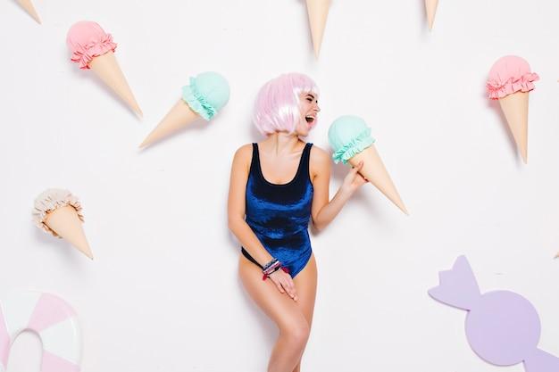 Ausdruck strahlend positiver gefühle der sexy jungen frau mit geschnittener rosa frisur, im badeanzug, der spaß mit riesigem eis hat. süßigkeiten, glück, verspieltes attraktives modell.
