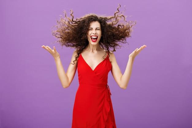 Ausdruck von innerer wildheit. porträt einer wilden und sorglosen, charmanten europäischen frau in stilvollem rotem abendkleid, die lockiges haar mit erhobenen händen hochschnippt und sich während der party laut lacht.