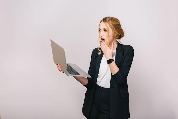 Ausdruck wahrer erstaunter gefühle der jungen hübschen blonden bürofrau, die mit laptop arbeitet. beschäftigt sein, nach lösungen suchen, überrascht, stilvoll aussehen