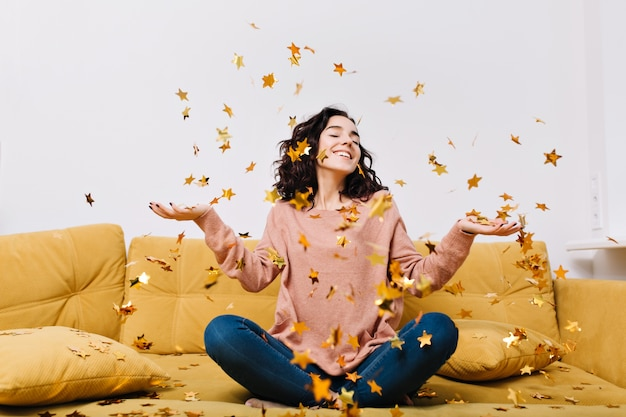 Ausdruck wahrer positiver gefühle der jungen freudigen frau mit geschnittenem lockigem haar, das spaß daran hat, lametta auf couch in der modernen wohnung zu fallen. home cosines, freude, lächeln