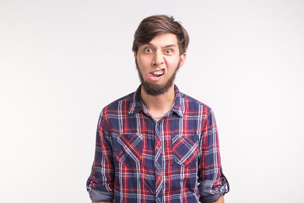 Ausdrucks- und gestenkonzept -junger mann streckt seine zunge isoliert auf weißem hintergrund heraus
