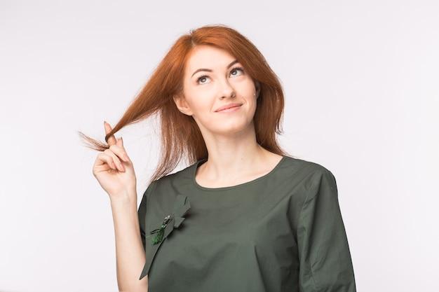 Ausdrucks- und personenkonzeptporträt einer schönen jungen frau mit den roten haaren, die über weiß nachdenken