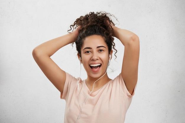 Ausdrucksstarke glückliche junge frau oder jugendlicher hat lockige afro-frisur, hört musik in kopfhörern,