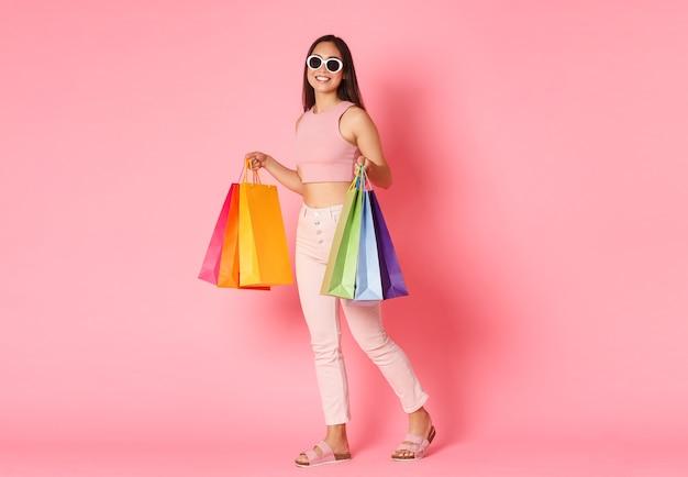 Ausdrucksstarke junge frau des porträts mit einkaufstaschen