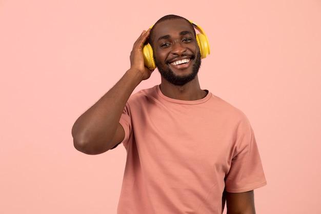 Ausdrucksstarker afroamerikaner, der musik über kopfhörer hört