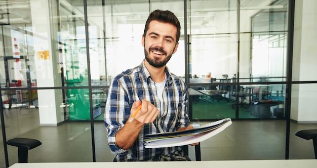 Ausdrucksstarker brünetter mann, der mit bleistift auf die kamera zeigt und lächelt