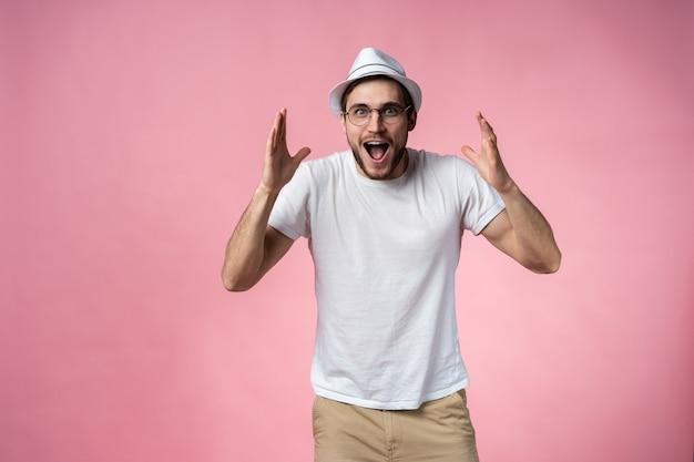 Ausdrucksstarker glücklicher überraschter mann, lokalisiert auf rosa.