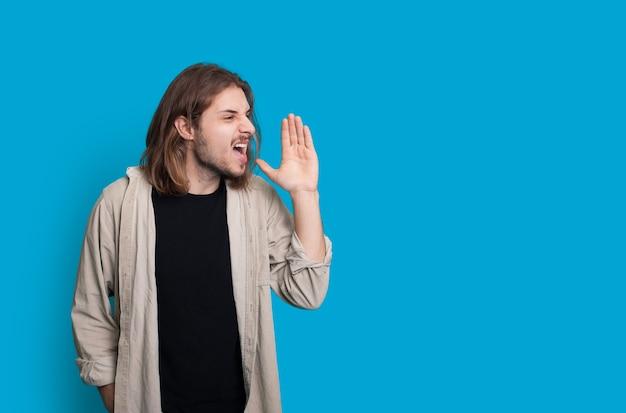 Ausdrucksstarker kaukasischer mann wirft auf einem blauen hintergrund mit leerzeichen auf, während er unglücklichen jemanden begrüßt