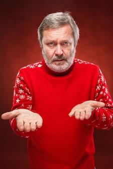 Ausdrucksstarker mann im roten weihnachtspullover