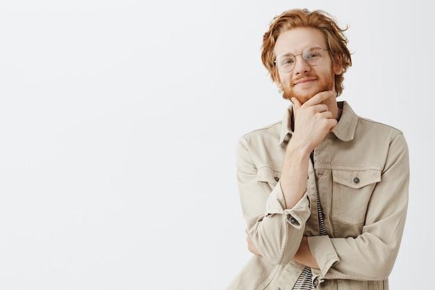 Ausdrucksstarker rothaariger kerl im beigen hemd