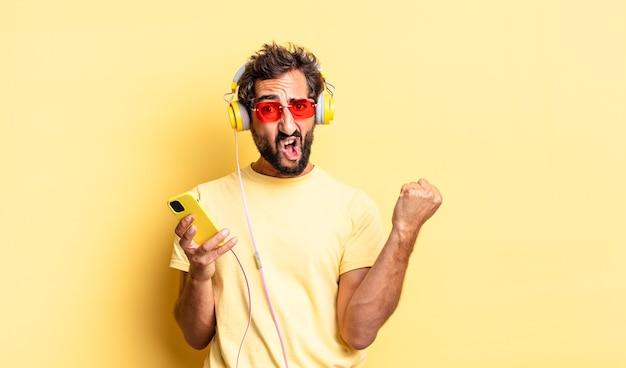Ausdrucksstarker verrückter mann, der aggressiv mit einem wütenden ausdruck mit kopfhörern schreit