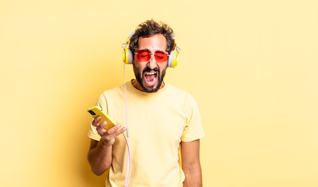 Ausdrucksstarker verrückter mann, der aggressiv schreit und sehr wütend mit kopfhörern aussieht