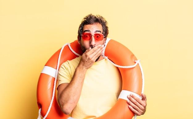 Ausdrucksstarker verrückter mann, der den mund mit den händen mit einem schockierten bedeckt. rettungsschwimmer-konzept