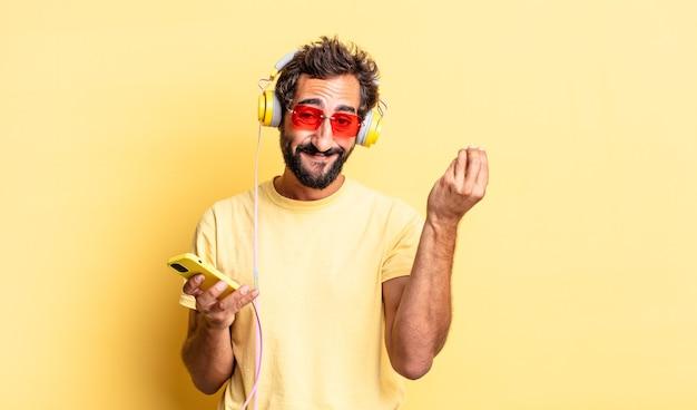 Ausdrucksstarker verrückter mann, der eine capice- oder geldgeste macht und ihnen sagt, dass sie mit kopfhörern bezahlen sollen