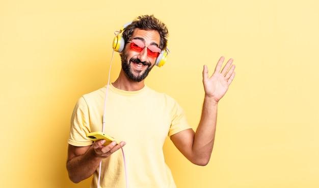 Ausdrucksstarker verrückter mann, der glücklich lächelt, die hand winkt, sie mit kopfhörern begrüßt und begrüßt
