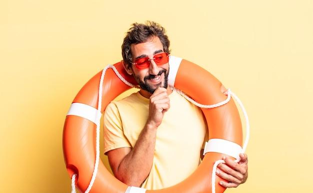 Ausdrucksstarker verrückter mann, der mit einem glücklichen, selbstbewussten ausdruck mit der hand am kinn lächelt. rettungsschwimmer-konzept