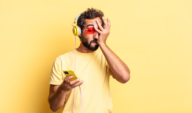 Ausdrucksstarker verrückter mann, der schockiert, verängstigt oder verängstigt aussieht und das gesicht mit der hand mit kopfhörern bedeckt