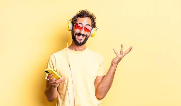 Ausdrucksstarker verrückter mann, der sich glücklich fühlt, überrascht, eine lösung oder idee mit kopfhörern zu realisieren