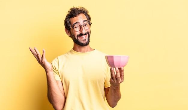Ausdrucksstarker verrückter mann, der sich glücklich fühlt, überrascht, eine lösung oder idee zu realisieren und einen topf zu halten
