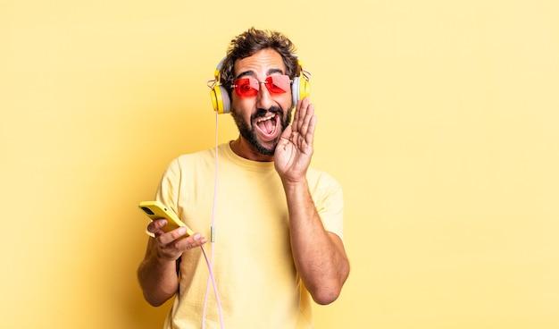 Ausdrucksstarker verrückter mann, der sich glücklich fühlt und mit den händen neben dem mund mit kopfhörern einen großen schrei ausstößt