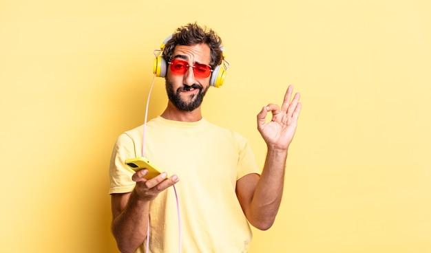 Ausdrucksstarker verrückter mann, der sich glücklich fühlt und zustimmung mit einer okayen geste mit kopfhörern zeigt