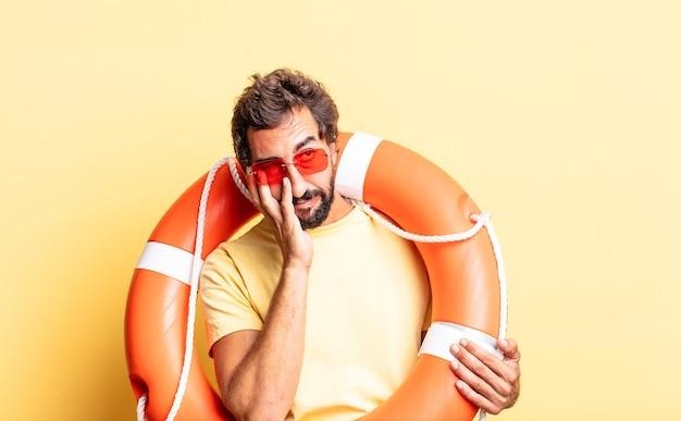 Ausdrucksstarker verrückter mann, der sich nach einem ermüdenden gefühl gelangweilt, frustriert und schläfrig fühlt. rettungsschwimmer-konzept