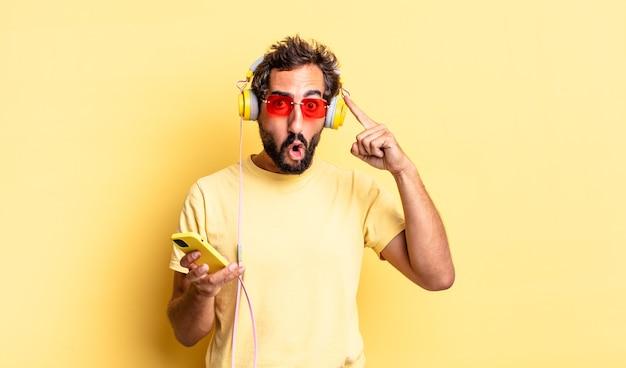 Ausdrucksstarker verrückter mann, der überrascht aussieht und einen neuen gedanken, eine neue idee oder ein neues konzept mit kopfhörern realisiert