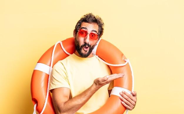 Ausdrucksstarker verrückter mann, der überrascht und schockiert aussieht, mit heruntergefallenem kiefer, der ein objekt hält. rettungsschwimmer-konzept