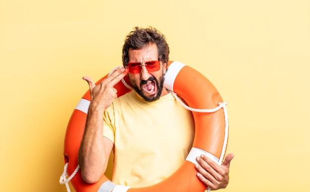 Ausdrucksstarker verrückter mann, der unglücklich und gestresst aussieht, selbstmordgeste, die waffenzeichen macht. rettungsschwimmer-konzept