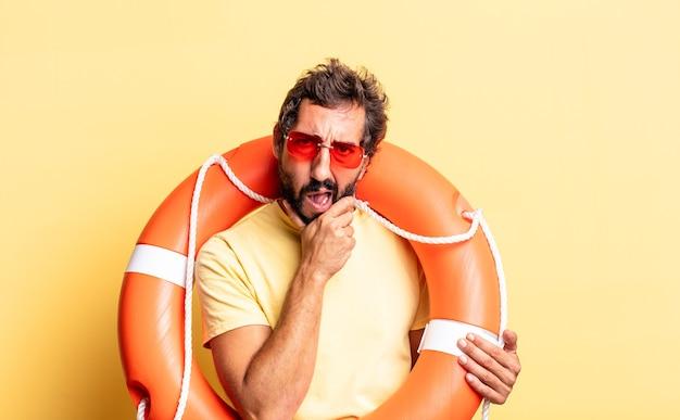 Ausdrucksstarker verrückter mann mit weit geöffnetem mund und augen und hand am kinn. rettungsschwimmer-konzept