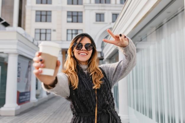 Ausdrücken von hellen positiven emotionen der modischen stadtfrau, die kaffee streckt, um auf sonniger straße zu gehen. schöne lächelnde frau in der modernen sonnenbrille, strickmütze, die spaß im freien hat.