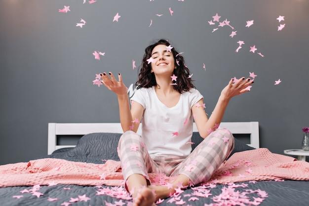 Ausdrücken wahrer positiver gefühle der jungen freudigen frau im pyjama mit geschnittenem lockigem haar, das spaß daran hat, rosa lametta auf bett in moderner wohnung zu fallen. gemütlichkeit zu hause, lächelnd mit geschlossenen augen