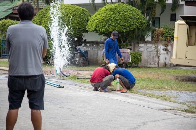 Ausfall des wasserversorgungssystems. handwerker reparieren wasserleitungen auf der straße.