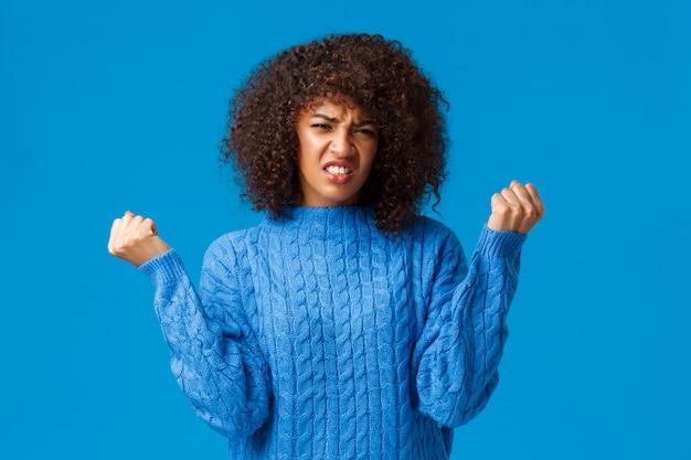 Ausfall, lebensstil und leutekonzept. verärgerte und düstere afroamerikanerfrauenballenfäuste wütend und verzieh das gesicht und hörten schlechte nachrichten, verlorene wette, gewannen nicht und standen beunruhigt und angespanntes blau