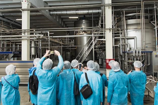 Ausflug in die fabrik. schutzleute, überschuhe, blaue overalls stehen und lauschen einem rundgang durch die metallbrauerei. menschen fotoproduktion am telefon