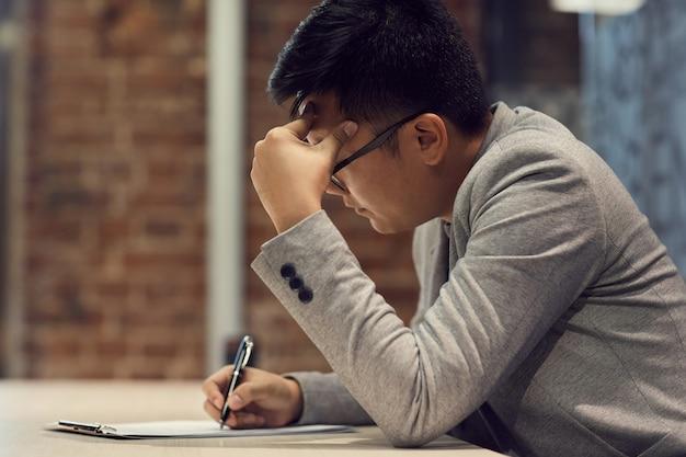 Ausfüllen des formulars des jungen asiatischen mannes im geschäftsbüro