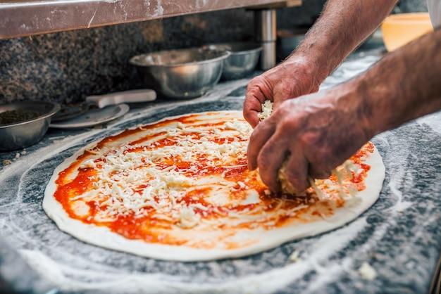 Ausgebreiteter käse des chefs auf pizzabasis. nahansicht.