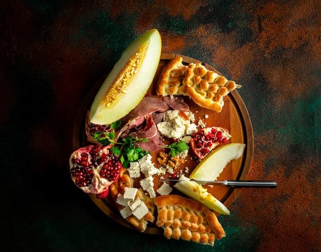 Ausgefallene fleisch- und käseplatte mit früchten als vorspeise