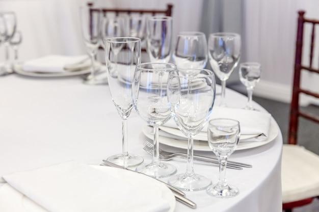 Ausgefallene tischdekoration zum abendessen mit serviettengläsern im restaurant, luxuriöser innentisch. elegante hochzeit bankettdekoration und artikel für lebensmittel, die vom catering-service auf einem weißen tischtisch arrangiert wurden.