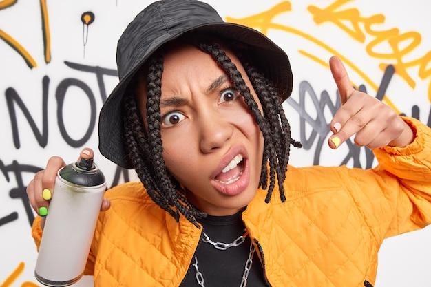 Ausgefallene trendige teenager-gesten cooles schild hält aerosolspray macht kreative zeichnungen an der straßenwand trägt modische kleidung. hipster-mädchen macht graffiti im urbanen outfit gekleidet